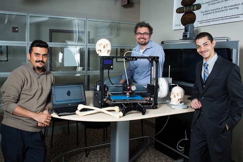 Amir Mosley '15 (right) researched 3-D printing  technology with help from Muneeb Mobashar (left)  of the Digital Education Collaborative and biology professor Dr. Björn Ludwar.