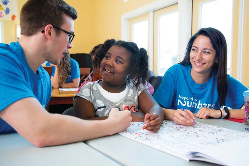 Andrew Law '17 and Gaby Tirado '18 chat and color with Makyia Johnson, 6.
