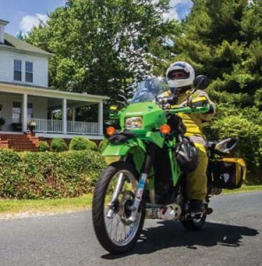 Perkins rides his Kawasaki dual-sport bike in front of his 110-year-old home in Prospect.
