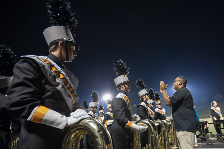 Andrew Snead '11, assistant director of the Powhatan High School marching band, provides last-minute instruction to students before their halftime performance.