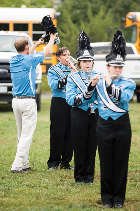 Adam Roach '04, band director at Eastern View High School in Culpeper County, was busy before the second football game in September. He had to repair the shako of freshman trombonist Everest Head, who was rehearsing with sophomore clarinetist Madison Tate (center) and senior piccolo player Daphne Sink.