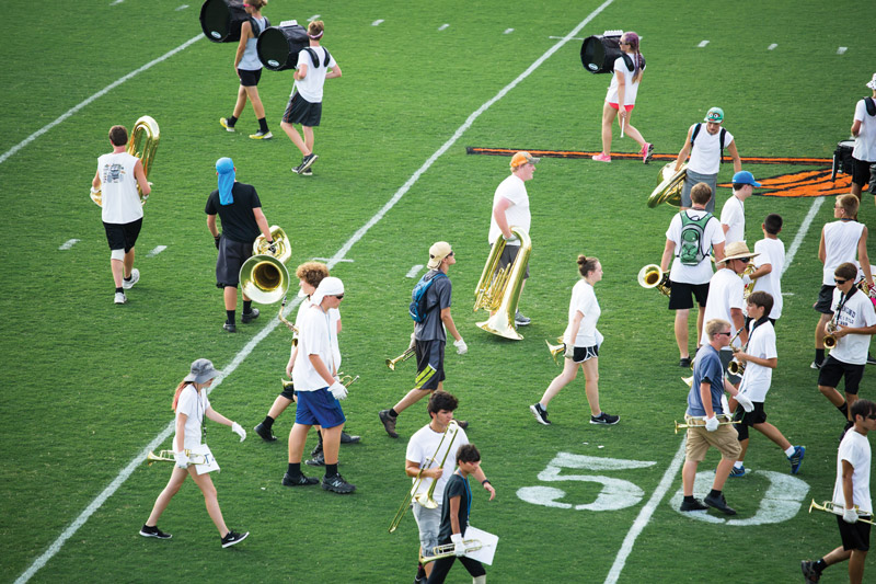 Despite the precision and polish that fans see at halftime shows, pre-game rehearsals, like this afternoon run-through at Powhatan High School, can appear more like chaos and confusion.