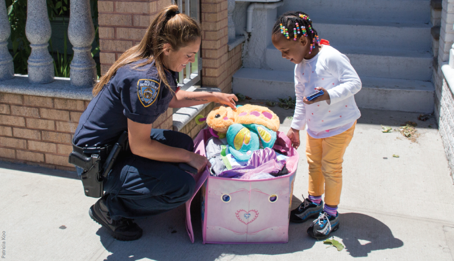 New York Police Department officer Valerie Cincinelli '06, a domestic violence officer, calls kids her 'soft spot.' Here she is delivering clothing and toys to Kadocia Pierre, a client in the Ozone Park neighborhood in Queens, New York.