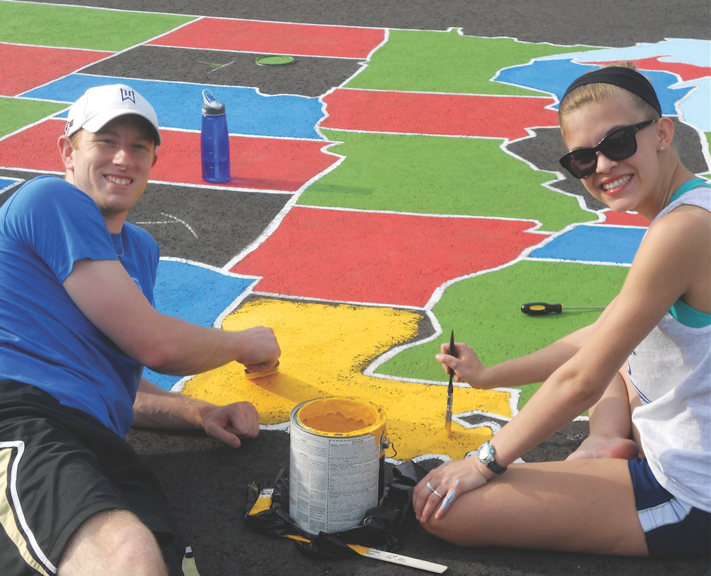 Kinesiology majors Chris Thornton '16, of Richmond, and Samantha Byers '16, of Toano, paint the state of Louisiana yellow on the U.S. map Longwood students created at Bacon District Elementary in Charlotte County. Courtesy of Dr. 'Vonnie' Colvin